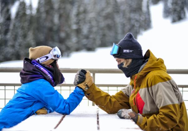 two people arm wrestling at ski resort